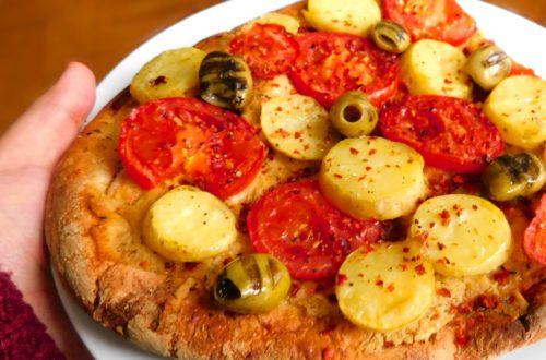 Belegter Fladen aus dem Ofen mit Tomaten, Kartoffeln und Hummus.